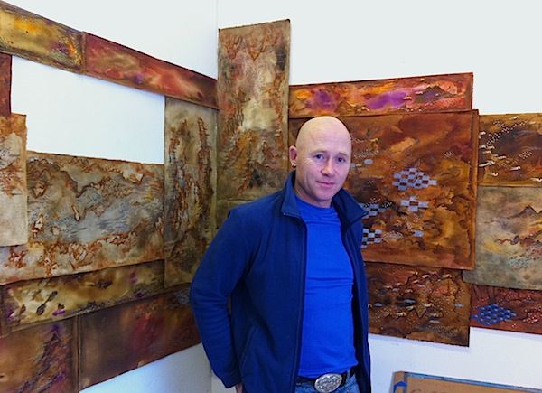 A portrait of the artist Caoimhghin Ó Fraithile his studio in Dingle. The photograph was taken by Ciarán Walsh, www.curator.ie. Caoimhghin is standing in front of a series of artworks.