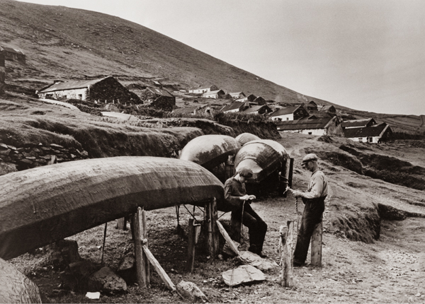 A photograph of the Great Blasket Island in the 1930s taken by Thomas H. Mason of Dublin. L-R: Domhnall Mharas Eoghan Bháin Ó Conchuir and Pádraig 'Ceaist' Ó Catháin who are mending currachs, the traditional boats used by the islanders. it features in The definitive book of photographs of the Great Blasket Island was published by Collins Press in June 2013. The book was authored by Michéal and Dáithí de Mórdha of Ionad an Bhlaoscaoid Mhóir and the photographs were edited by Ciarán Walsh of curator.ie. It also features in an exhibition of the same name.