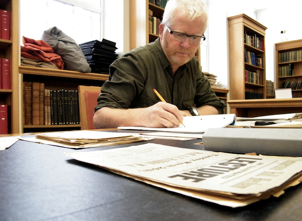 Ciaran Walsh researching the Haddon papers in Cambridge University Library. The photograph shows freelance curator Ciarán Walsh at work in the Manuscripts Room in the Library. He is surrounded by documents from one of the files containing uncatalogued material dating form the early 1890s when Haddon was active in the Irish Ethnographic Survey 1891-1903, the subject of the 'Irish Headhunter' project curated by Ciarán Walsh in 2012/3. He is trying to piece together the archive of the Irish Ethnographic Survey as part of a research project called 'Haddon in Ireland.' a project being developed in association with the Museum of Archaeology and Anthropology in Cambridge and NationalUniversity of Ireland Maynooth. The research was funded by the Heritage Council of Ireland.