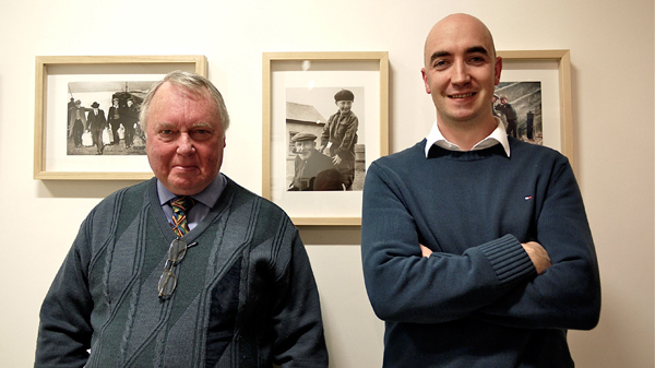 Gearóid Cheaist Ó Catháin and Daithi De Mordha standing in front of a photograph taken of Gearóid shortly after the Great Blasket Island was evacuated (1953).