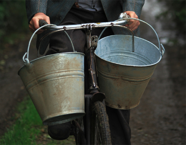 "A still from the shoot by  Ciarán Walsh \ www.curator.ie showing Thomas O'Sullivan carrying steel buckets  on the handlebars of an old bike as he cycles along a rural laneway in County Kerry, Ireland. Ciarán Walsh was shooting 'Drawing the Water' for artist Pauline O'Connell, a 5 minute film that deals with the tasks associated with collecting water. ""It's an intense reflection on the importance of water, the rhythm of the task of collecting it and the sensuous quality of washing by hand"" says Walsh who spent three days filming the piece."