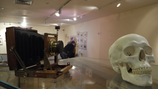 The photograph shows the 'Headhunter' exhibition being installed in The National Museum of Ireland. It features a half plate field camera (c 1895) and a skull sitting on top of a display case while members of the museum's staff hang the photographs of Charles R Browne in the background. The exhibition was developed by Ciarán Walsh of EYEBALL publishing,web www.curator.ie, an independent curator based in Balltheigue, Co Kerry, Ireland. It was developed with Dáithí de Mórddha of Ionad an Bhlascaoid Mhóir,Blasket Centre, Dún Chaoin, with funding from the OPEW and the Heritage Council.