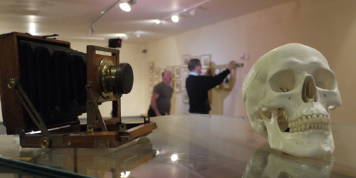 Skull and Camera 2013: the photograph shows The installation of the 'Irish Headhunter' exhibition in the National Museum of Ireland, Castlebar, Co. Mayo. The photography shows a skull and a camera on a display case with men hanging pictures in the background. The photograph was published by Ciarán Walsh of www.curator.ie, a heritage project management company based in Ballyheigue, Tralee, Co. Kerry, Ireland. It was exhibited all over Ireland and in England as part of the exhibition, The Irish Headhunter, the photograph albums of Charles R. Browne' (2012/2013). 'The Irish Headhunter' project (anthropology and photography) was developed in association with TCD, Triniity College Dublin, The National Museum of Ireland, Royal Irish Academy, Cambridge University, Museum of Archaeology and Anthropology Cambridge, National University of Ireland Maynooth, Oireachtas na Gaeilge and Áras Éanna, the Áran Islands. Funded by the Heritage Council of Ireland and the OPW (Office of Public Works) through The Great Blasket Centre, Dingle.