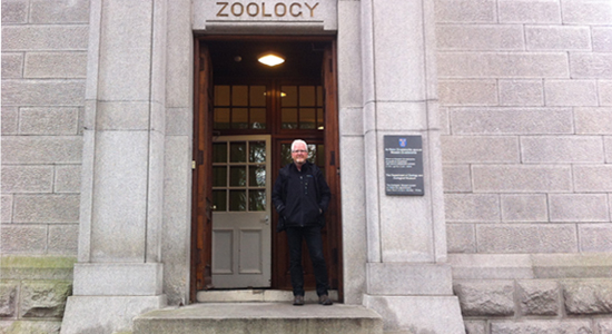 "This photograph shows Ciarán Walsh in the doorway of a stone building, the entrance to the Zoology Dept. TCD. The word ""Zoology"" is carved above the door. The photograph was taken in December 2015 by Siobhan Ward. Walsh is director of www.curator.ie and is a research scholar on a joint project with Maynooth University and TCD, funded by the research Council of Ireland. Ward is the Chief Technical officer in the Anatomy Dept., School of Medicine, TCD. They have recreated a photograph of D. J. Cunningham, Professor of Anatomy TCD, that was taken in the same spot 125 years ago. Walsh and Ward are working together on the resolution of the collection of the Anthropometric Laboratory TCD that was discovered in 2014."