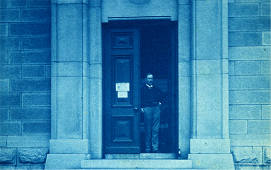 "This photograph shows Prof. Daniel J. Cunningham, who held the Chair of Anatomy TCD from 1883 - 1903. He is shown standing in the doorway of a stone building, the entrance to the Zoology Dept. TCD. The word ""Zoology"" has since been carved above the door. The photograph was taken around 1891 by Charles R. Browne. Ciarán Walsh and Siobhan Ward have recreated this photograph to mark the commencement of work on the resolution of the collection of the Anthropometric Laboratory established by Cunningham and Alfred Cort Haddon in 1891. The collection was thought to have been dispersed in 1949 but it was rediscovered in storage in 2014. Walsh is director of www.curator.ie and is a research scholar on a joint project with Maynooth University and TCD, funded by the research Council of Ireland. Ward is the Chief Technical officer in the Anatomy Dept., School of Medicine, TCD."
